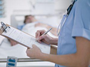 a nurse writing on a notepad
